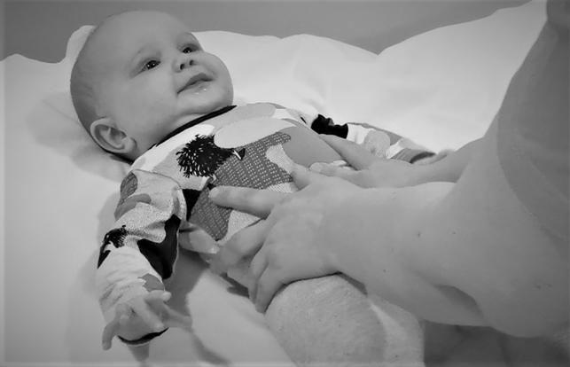 Kuvassa äiti hieroo vaatteiden päältä vauvan vatsaa.